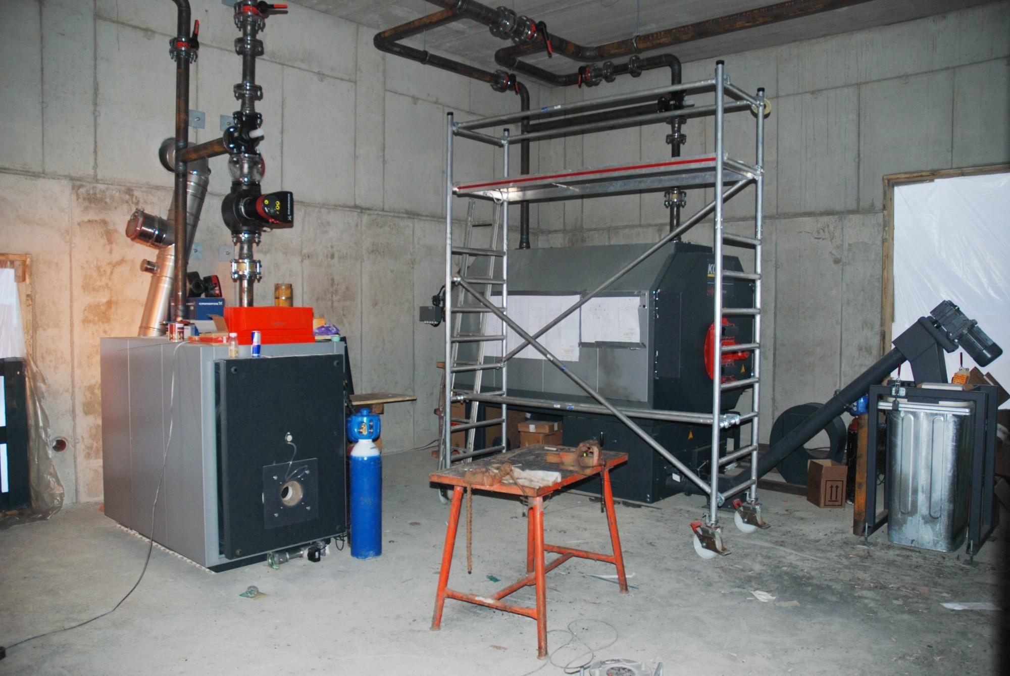 Das Bild zeigt das Innere des Heizwerkes mit dem Gaskessel und Pelletkessel
